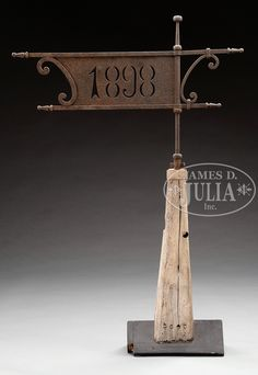 "FINE DIMINUTIVE SHEET IRON ""1898"" BANNER WEATHERVANE. Circa 1898, American. The bannerette with central dated iron sheet joined to C-scroll elements within a simple framework with turned iron finials swiveling on iron rod within ringed spacers terminating in a suppressed ball finial mounted on a tapering square roof finial with iron band in old white paint, early if not original to bannerette. Now mounted on a simulated wood peaked rooftop stand."
