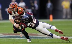 Cincinnati Bengals' Andy Dalton (14) is hit by Houston Texans' D.J. Swearinger (36) during the first quarter of an NFL football game, Sunday, Nov. 23, 2014, in Houston. (AP Photo/Patric Schneider)