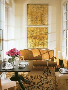 Living com sofá marron em camurça e  dois quadros