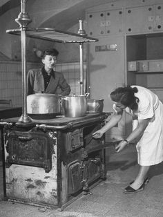 Mrs. Michael Stern Inspecting an Old Fashioned Wooden Kitchen Stove