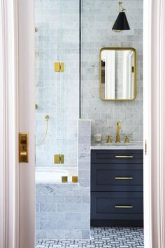 Marble tiled pony wall next to a black washstand features antique brass pulls complimenting a polished brass vintage faucet, brass shower accents, and a curved brass vanity mirror.
