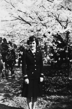 Louise Nash Dorsett stands in front of a tree wearing a WAVES officer dress blue uniform and garrison cap in spring of 1945 ~