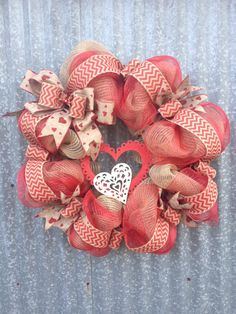24 valentines wreath mad with burlap mesh and red deco mesh. Adorned with chevron burlap ribbon and natural heart linen ribbon. One large red