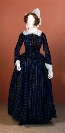 Checked silk satin dress, Scottish, c. mid-1840s. By 1840 fancy checks and stripes were popular and they were exploited in the cut of the bodice so that their lines emphasised a narrow waist. As the fullness of skirts became greater in the 1830s, the widths used increased and the total amount of fabric needed crept up, making clothes more expensive. To hold the skirts out, several petticoats were needed, making dresses quite heavy.