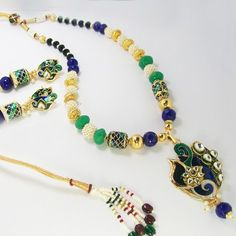 This meenakari necklace is based on a copper pendant polished in high gold and covered in meenakari / enameling in multiple colors.