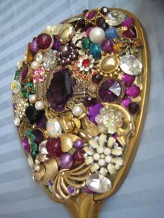 love all the vintage jewelry on this hand-mirror