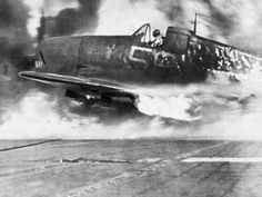 Wounded pilot sits in the cockpit after landing in his flaming plane on the fiery deck of a carrier hit by a Japanese kamikaze in the Pacific, June 28, 1945. The airman was saved.