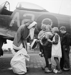 Santa Claus (Leading Aircraftman Fred Fazan from London) hands out presents to Dutch children at Volkel, 13 December 1944. Members of No 122 Wing had saved their sweet ration for weeks, and contributed enough money to give the children their first proper Christmas party. It was noted by the photographer that this year Santa was afraid of Messerschmitts, so he decided to come by RAF Tempest!