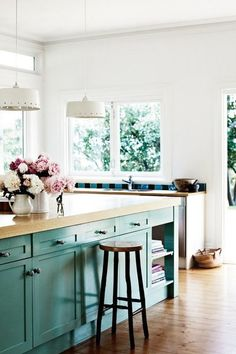 Bright and airy kitchen with seafoam green cabinets, white pendant lights and fresh flowers.