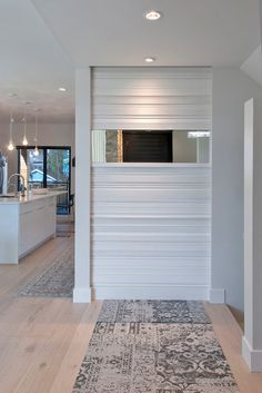 """Pretty simple and interesting. 'a textured feature wall in the entry. Katie created the wall by mounting lengths of baseboard. """"I selected various profiles of baseboard, nailed them to the wall, filled the holes, caulked the edges and painted it,"""" she says.'"""