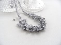 Hand crocheted with metalized silver viscose yarn and beaded with silver colored Swarovski Crystals this necklace is light and comfortable to