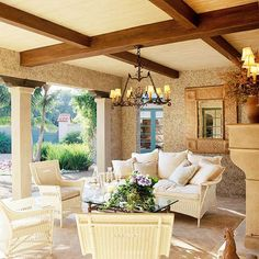 Hang a Chandelier for a Formal Look-A wrought-iron chandelier with candle lamps turns this covered patio into an elegant outdoor living room. Matching sconces over the fireplace complete the illusion that the living room has moved outdoors