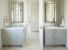 Cream herringbone floor tiles framing complement a white shiplap bathroom door flanked by gray apothecary style bath vanities finished with glass knobs and white marble countertops with polished nickel faucets positioned under beaded beveled vanity mirrors mounted on a wall adjacent to polished nickel towel rings.