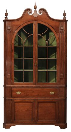 Important North Carolina Federal Carved Walnut Corner Cupboard - attributed to John Swicegood, Davidson County, North Carolina, circa 1800, single-case construction, broken-arch pediment with carved rosettes & set with three original turned finials over arched glazed doors opening to fixed shelved painted interior & flanked by moldings & carved devices, lower frieze over a single dovetailed drawer with line-inlaid drawer front & two cabinet doors, inlaid teardrop escutcheons, 106 x 55 x 23…