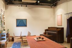 柴原さんの作品やニューヨークスタインウエイアップライトのリメイクピアノが並ぶギャラリー。壁のテキスタイルの額は妻の柴原規子さんの作品。