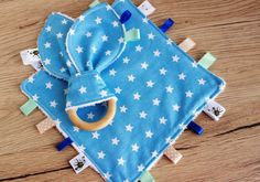 Taggie, New baby boy gift, Sensory blanket, Baby teether, Baby comforter, Baby boy lovey, Security blanket, Doudou, Star baby shower gift  GIFT SET INCLUDES:  ♥♥ Taggie blanket. The baby comforter measure 7.5 each side. (18*18cm). This teething blanket is made from blue star print cotton fabric design on the one side and white terry towelling on the other.  ♥♥ Baby teething toy - Bunny ear teether. The ring is 2,5 in diameter, making it the perfect size for babys little hands.  If your item…