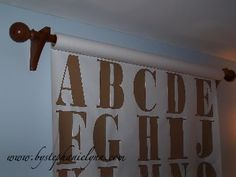 Roll of oversized paper, hung from a curtain rod, large letters cut from brown kraft paper - fun for a playroom space, and easy to change out