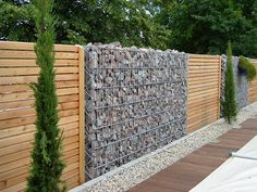 Gabion Wall Stone and Wood Fence. Along the fence line Backyard Fences, Fenced In Yard, Garden Fencing, Mesh Fencing, Garden Trellis, Outdoor Spaces, Outdoor Living, Gabion Retaining Wall, Gabion Baskets