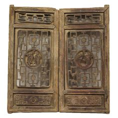 Pair of Chinese Pine Fretwork Cabinet Door Panels/Shutters  Each door has a fretwork panel at the top rail above a large fretwork panel centered with a round medallion, hand carved with a scene of two figures in traditional dress. At the bottom, the doors are decorated with a solid panel carved with a geometric design in relief. 19th century