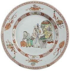 Assiette peinte dans les émaux de la famille verte à décor de figures en porcelaine de Chine de la Compagnie des Indes d'époque Kangxi. Assiette à décor émaillé polychrome et or dans les émaux de la famille verte, le bassin peint d'un vieil homme accompagné de son porteur d'eau et entouré de jarres. Sur le marli et l'aile, attributs du lettré et frise de croisillons.