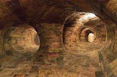 O artista brasileiro Henrique Oliveira criou uma instalação labirinto de madeira que se estende por corredores do Museu de Arte Contemporânea da Universidade de São Paulo.   A instalação massiva permite aos visitantes caminhar por seus túneis de madeira, criando uma experiência intrigante que estimula os sentidos da visão, audição e olfato.