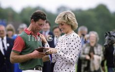 June 27, 1987: Princess Diana presenting a medal to Prince Charles at a polo match at Smith's Lawn Polo Field, Windsor, Berkshire.