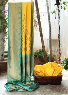 DIVINE YELLOW IS WOVEN WITH DIAGONAL GOLD AND SILVER TOWARDS THE PALLU. THE SEA BLUE IRIDESCENT YELLOW WITH GOLD BORDER AND PALLU GIVES THIS SAREE RAVISHED FINISH.