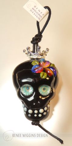 "RWD shiny black lampworked glass calavera sugar skull focal bead with handmade murrini eyes, ""opal"" floral detail and tiny silver crown. $45 - sold"