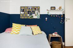 Quarto infantil com meia parede pintada de azul marinho e almofadas estampadas e coloridas.