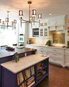 Chandeliers in kitchen, high cabinets. Love the dark island with the open shelving for recipe books, etc.