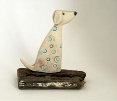 Shirley hand built the little dog with earthenware clay. Bisque fired, then hand coloured with under glazes and oxides. Then fired again at a higher temperature. Patterns and colours may vary slightly as each piece is had formed and built. No moulds are used.. Please note this piece is made to order and takes between 4 - 6 weeks delivery. Assembled onto a piece of selected with driftwood. Each piece of driftwood will vary. 11cm x 8cm. £49.00. Can be seen at Shirley Vauvelle Studio.