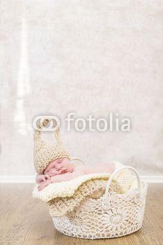 Newborn kleines Mädchen in einem Häkelkorb mit Mütze