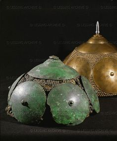 HALLSTATT CULTURE HELMET 10TH-6TH BCE Two wicker-work helmets plated with bronze calottes 1) Foreground: from a tumulus in Smrjeta, size: 29 cm 2) Background: reconstruction by Th. Bell in 1883 Smrjeta, Slovenia Naturhistorisches Museum, Vienna, Austria