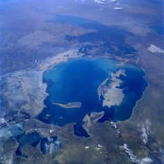https://flic.kr/p/fg2aEa | sts047-079-083 | STS047-079-083  Aral Sea, Kazakhstan and Uzbekistan  September 1992 A much depleted Aral Sea (refer to the July 1985 photograph STS-51F-036-0059) can be seen in this south-looking, low-oblique view.  The emerging, pointed island of Barsa-Kel'mes and the expanding, broad Vozrozhdeniya Island are visible in the center of the sea.  Vozrozhdeniya Island is expanding southward toward the Amu Darya River Delta and northward toward the growing Kulandy…