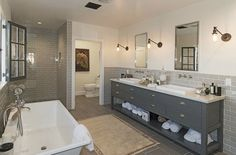 Gray subway tile behind sinks and in shower makes this bathroom