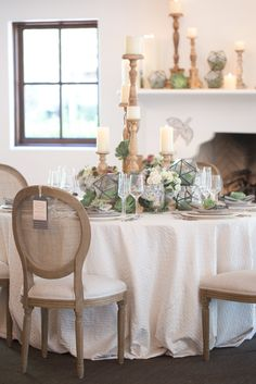 Blush pink roses, white hydrangeas, large round succulents. Glass and wooded candelabras and geometric shapes.
