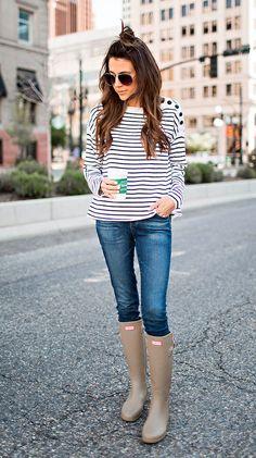 Christine Andrew parada nas ruas veste blusa de manga comprida de listras, calça jeans skinny e galochas areia