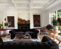 The combination of black chesterfields and white walls gets a warm update from leather and mahogany touches.