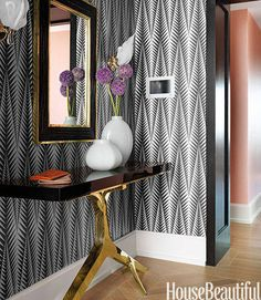 Designer Jamie Drake took cues from the geometric patterns and bold spirit of the building's lobby, covering the New York City apartment's foyer walls in Clarence House's Neisha Crosland Zebra. Rose console, Hudson Furniture. Nairobi mirror, Flair Home Collection. Bai jade vases, Robert Kuo.   - HouseBeautiful.com