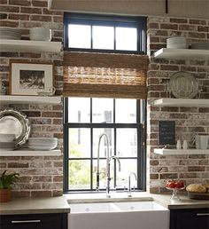 Modern style meets old-world charm... exposed brick kitchen backsplash with open shelving over apron sink and gray cabinets.