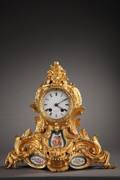 A small gilt bronze Rococo clock richly decorated with foliage, acanthus leaves, scrolling foliage and godroon resting on a waving base. The main face of the clock is adorned with...