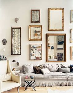 This pretty living room is perfectly designed w/ a gallery wall made of mirrors (mostly)! A low to the ground gray couch & wood floors make this space feel oh-so comfy!