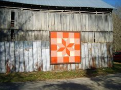 """PAINTED IN BRIGHT orange and white, this heritage """"Blazing Star"""" pattern highlights a family farm barn. On the Appalachian Quilt Trail's """"Big Haley"""" route, """"Blazing Star"""" can be seen after a drive down a country road along the Clinch River."""