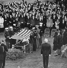 11/25/63: Jacqueline and Robert Kennedy watch the final rites for JFK.  Usually only six pallbearers were needed, but JFK's casket was so heavy, two additional men were added to the detail.