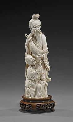 """Well carved, early 20th Century, Chinese ivory group; of two bearded sages, one standing and holding a fish, the other seated with a staff; H: 9 3/4"""", wood stand"""