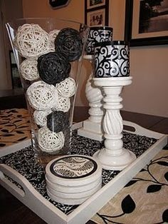 getting some ideas for centerpieces.. love the candle stands and votive holders... the raffia balls I'd do red black and silver or white love the vase idea.. and minus the tray and coasters ..