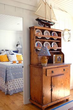 seaworthy cabinet - love the Pierre Deux lampshade and pillows on the bedroom to the right.  GREAT look!