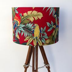 Large drum lampshade covered with red tropical parrot fabric. Gorgeous deep red background with green tropical leaves and colourful parrots. Shade is 28cm wide x 20cm highHandmade in Australia Shade only, base not included