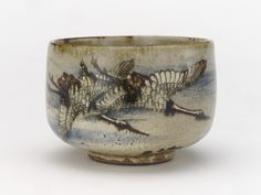 Tea bowl with design of cranes and chrysanthemums, early 18th century.   Ogata Kenzan , (Japanese, 1663-1743). Edo period. Buff clay; white slip, iron and cobalt pigments under transparent glaze. H: 7.2 W: 10.4 D: 10.4 cm. Kyoto, Japan. The combination of crane and chrysanthemum has two possible but interrelated nuances. First, it is an auspicious combination, symbolize longevity. Second, may refer to poems of birds and flowers of the twelve months by Kamakura period poet Fujiwara Teika.