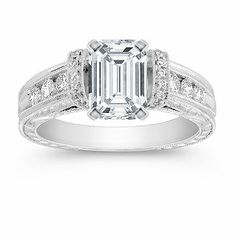 This gorgeous vintage inspired cathedral engagement ring features 26 round, hand-matched diamonds, at approximately .40 carat total weight. The elegant design is crafted from quality 14 karat white gold with hand-engraved side detailing. Personalize the look by adding a center diamond in the shape and size of your choice. Shown with a center stone Emerald Cut Diamond.